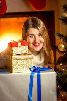 Nahaufnahmeporträt der schönen lächelnden frau, die mit weihnachtsgeschenken am kamin aufwirft