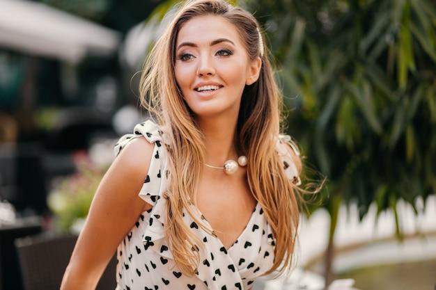 Nahaufnahmeporträt der schönen lächelnden frau gekleidet im weißen bedruckten kleid im romantischen stil, der im straßencafé am sonnigen tag aufwirft