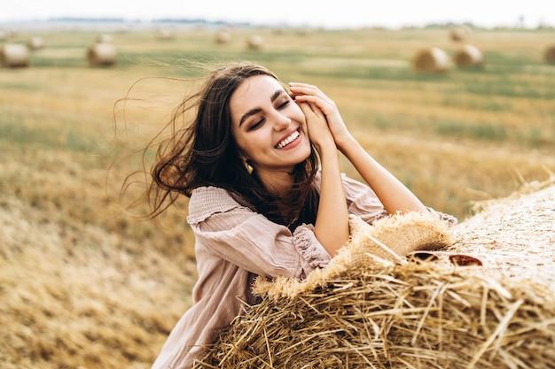 Nahaufnahmeporträt der schönen lächelnden frau mit geschlossenen augen. die brünette stützte sich auf einen heuballen. ein weizenfeld auf dem hintergrund