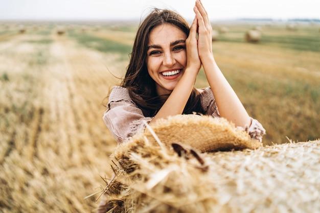 Nahaufnahmeporträt der schönen lächelnden frau mit geschlossenen augen. die brünette stützte sich auf einen heuballen. ein weizenfeld Premium Fotos