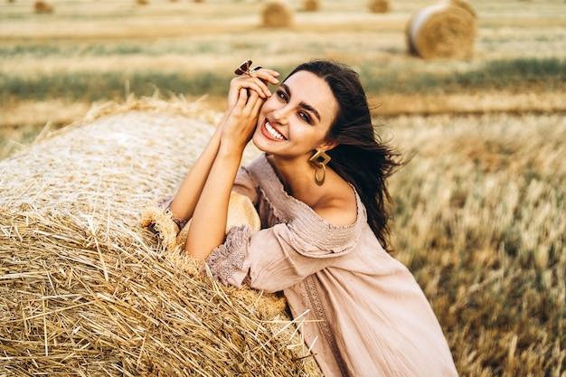 Nahaufnahmeporträt der schönen lächelnden frau mit geschlossenen augen. die brünette stützte sich auf einen heuballen.