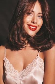 Nahaufnahmeporträt der schönen lächelnden sinnlichen brunettefrau. mädchen in der eleganten beige klassischen kleidung. modell mit den roten lippen lokalisiert auf schwarzem