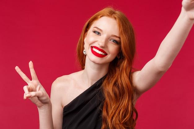 Nahaufnahmeporträt der schönen rothaarigen europäischen frau, die ihren geburtstag feiert oder partei genießt, selfie mit friedenszeichen nehmend und zufriedenes lächeln strahlend, spaß, rote wand habend