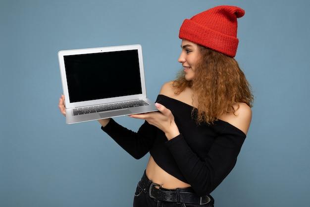Nahaufnahmeporträt der schönen selbstbewussten dunkelblonden gelockten jungen frau, die laptopcomputer hält