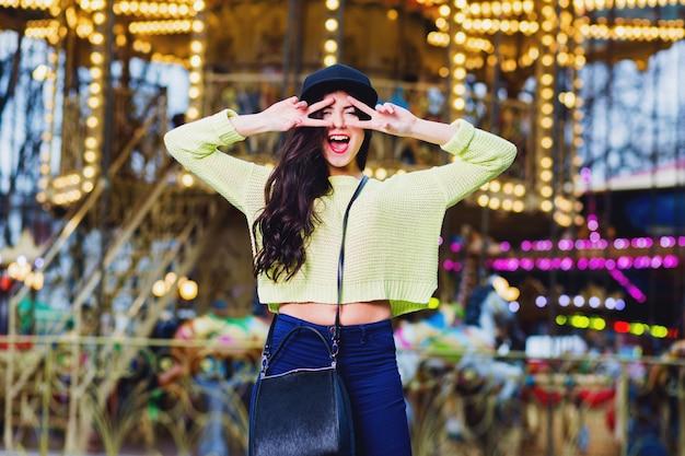 Nahaufnahmeporträt der sexy ausgefallenen stilvollen frau haben spaß und lächeln auf attraktionen. trägt einen trendigen schwarzen hut mit hipster-beute und einen neonpullover.