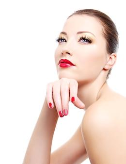 Nahaufnahmeporträt der sexy jungen kaukasischen jungen frau mit goldenem glamour-make-up und roter heller maniküre