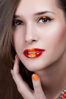 Nahaufnahmeporträt der sexy kaukasischen jungen frau mit goldenem zaubermake-up und roter heller maniküre