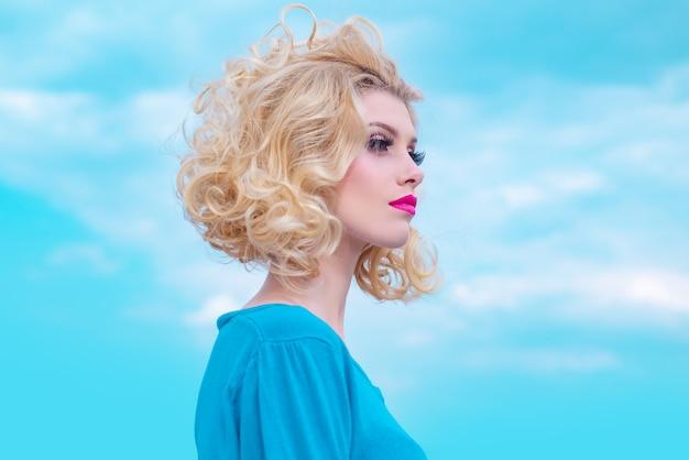 Nahaufnahmeporträt der sexy kaukasischen jungen frau mit schönen blauen augen. auf himmelshintergrund.