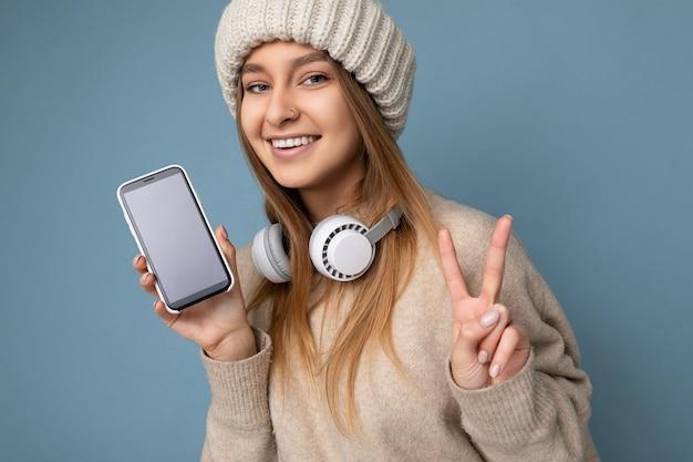 Nahaufnahmeporträt der sexy schönen positiven lächelnden jungen blonden frau, die beige strickjacke trägt und
