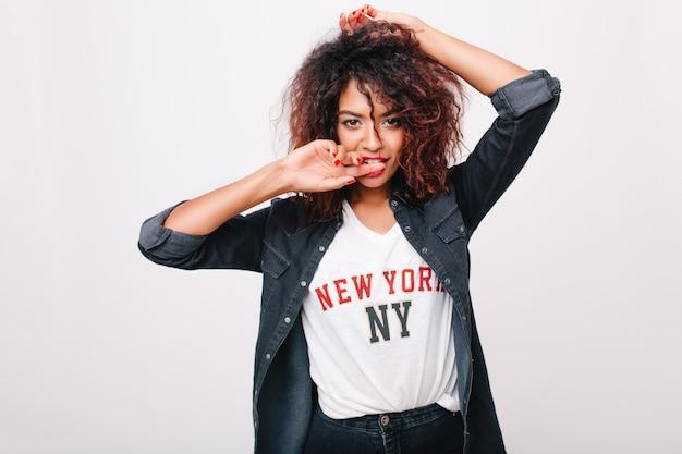 Nahaufnahmeporträt der sinnlichen mulattin in der jeansjacke lokalisiert. innenfoto des lockigen brünetten mädchens, das spielerisch aufwirft und ites finger.