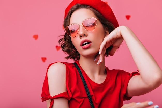 Nahaufnahmeporträt der sinnlichen nachdenklichen frau in der roten baskenmütze. modisches ernstes mädchen mit dem kurzen haarschnitt, der aufwirft.