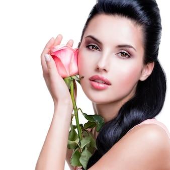 Nahaufnahmeporträt der sinnlichen schönen frau mit rosa rose auf weißer wand.