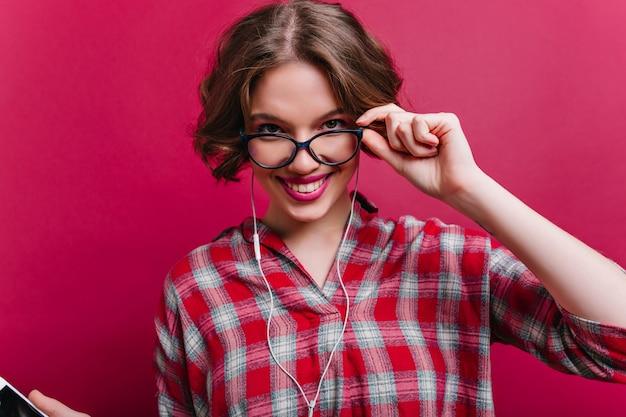 Nahaufnahmeporträt der sinnlichen stilvollen frau im karierten hemd trägt brille. innenfoto des sorglosen lockigen mädchens, das auf rotweinwand aufwirft.