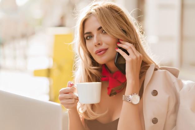 Nahaufnahmeporträt der spektakulären blonden frau, die kamera mit interesse beim telefonieren betrachtet