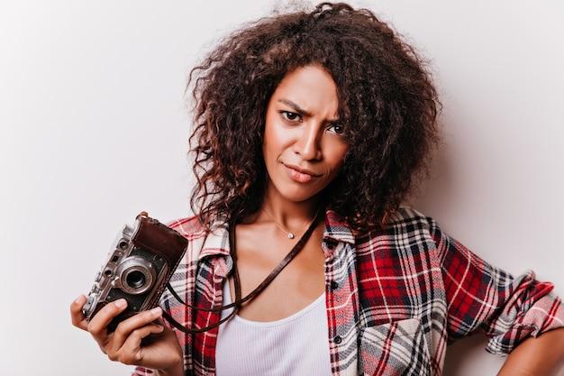 Nahaufnahmeporträt der unzufriedenen lockigen frau, die weinlesekamera hält. atemberaubende weibliche shotgrapherin, die in der selbstbewussten haltung steht.