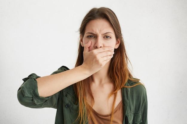 Nahaufnahmeporträt der verschlafenen hausfrau, die ihren mund mit der hand bedeckt, während gähnt, müde zu sein