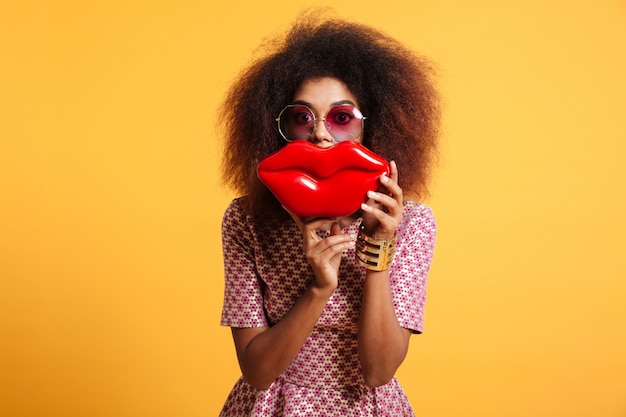 Nahaufnahmeporträt der verspielten afrikanischen frau in der sonnenbrille, die große rote lippen vor ihrem gesicht hält