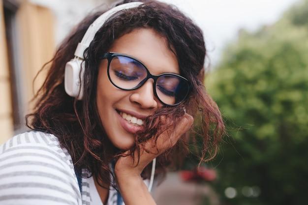 Nahaufnahmeporträt der verträumten jungen dame mit hellbrauner haut, die lieblingslied genießt