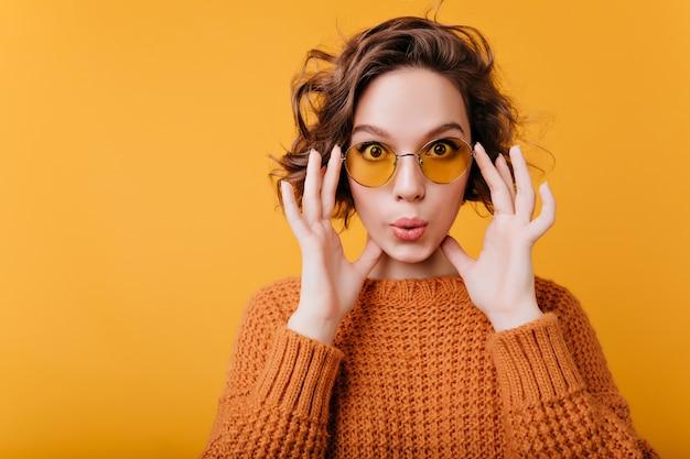 Nahaufnahmeporträt der weißen lustigen frau in den gelben weinlesegläsern