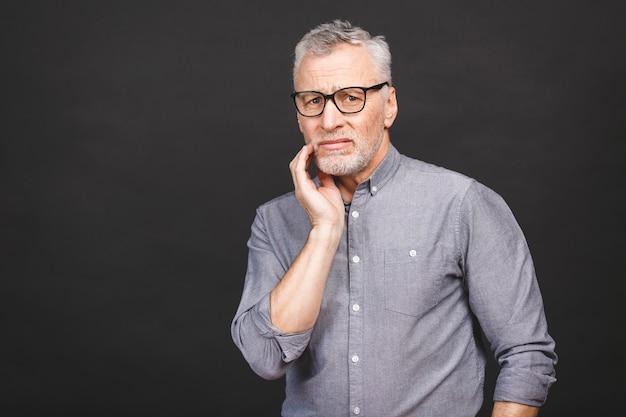 Nahaufnahmeporträt des älteren gealterten mannes, der unter zahnschmerzen auf schwarzem hintergrund leidet.