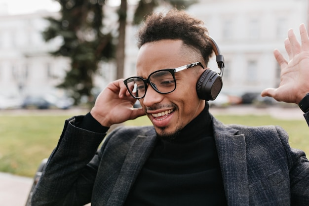 Nahaufnahmeporträt des afrikanischen kerls in der guten laune, die lieblingsmusik genießt. foto im freien des fröhlichen schwarzen mannes mit lachendem lockigem haar, während auf bank ruhend.
