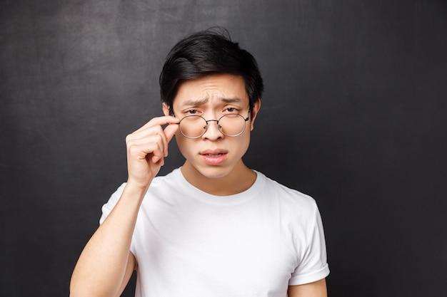 Nahaufnahmeporträt des arroganten skeptischen asiatischen mannes im weißen t-shirt, zusammengekniffen mit zweifel abnehmende brille, um person näher zu betrachten, die seltsamen unsinn spricht, stehend