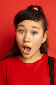 Nahaufnahmeporträt des asiatischen teenagers lokalisiert auf rotem studiohintergrund