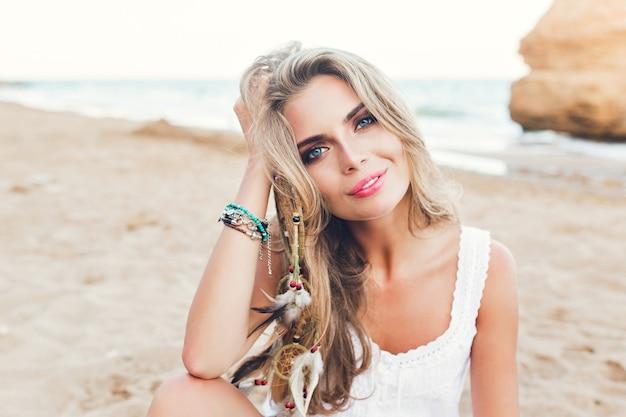 Nahaufnahmeporträt des attraktiven blonden mädchens mit den langen haaren und den blauen augen, die am strand sitzen. sie schaut in die kamera.