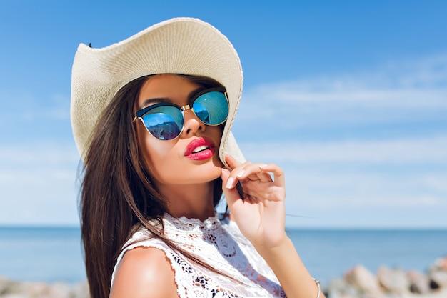 Nahaufnahmeporträt des attraktiven brünetten mädchens mit dem langen haar, das am strand nahe meer steht. sie schaut in die kamera.