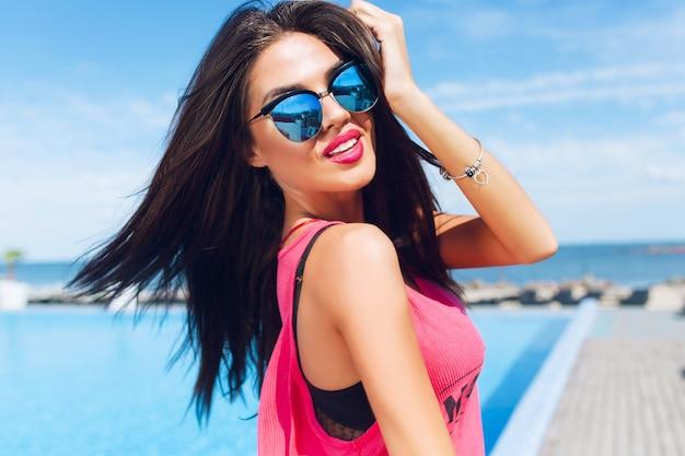 Nahaufnahmeporträt des attraktiven brünetten mädchens mit dem langen haar, das nahe pool steht. sie berührt haare und schaut in die kamera.