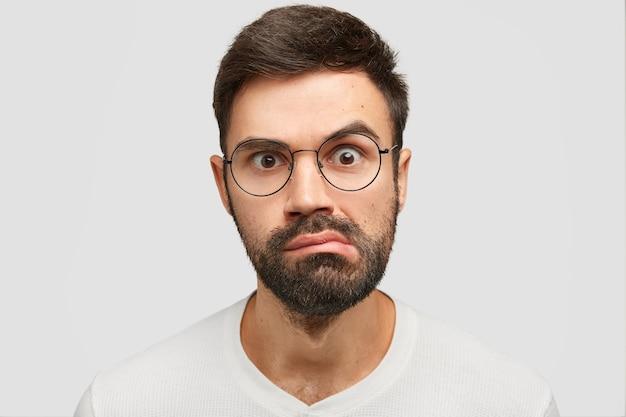 Nahaufnahmeporträt des attraktiven jungen mannes mit dunklen stoppeln, sieht überraschend aus