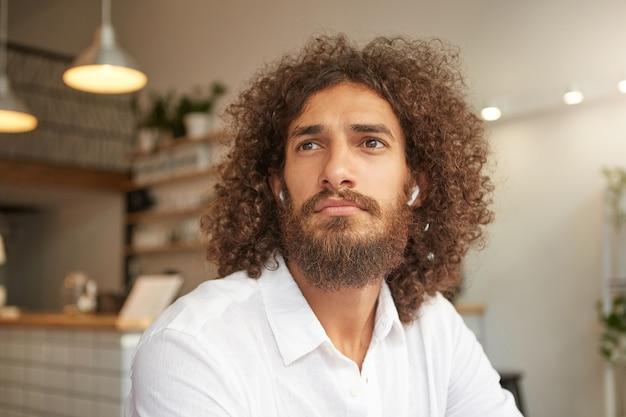 Nahaufnahmeporträt des attraktiven lockigen kerls mit üppigem bart, der über caféinnenraum aufwirft, kopfhörer und weißes hemd trägt, nachdenklich beiseite schaut und auf seine bestellung wartet