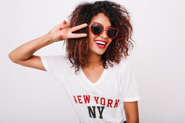 Nahaufnahmeporträt des attraktiven schwarzen weiblichen modells mit der isolierten roten maniküre. foto des glücklichen afrikanischen mädchens in der sonnenbrille, die mit friedenszeichen aufwirft.