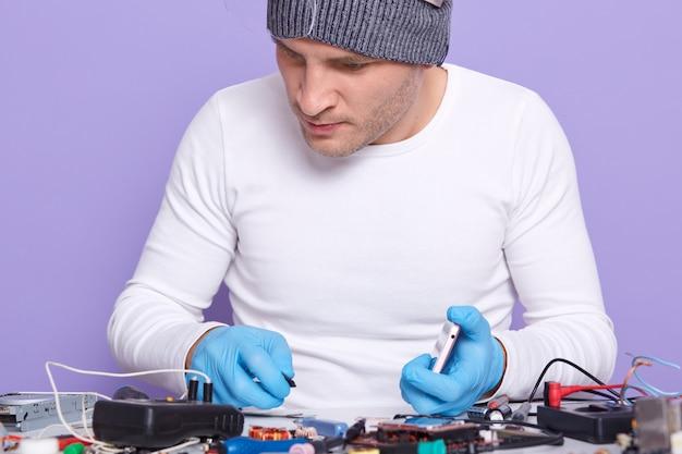 Nahaufnahmeporträt des aufmerksamen gut ausgebildeten elektronikingenieurs, der reparatur tut