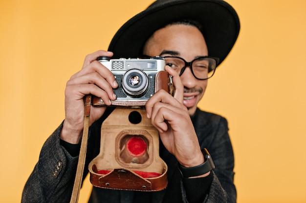 Nahaufnahmeporträt des begeisterten mulattenmannes, der arbeit genießt. trendy männlicher fotograf, der spaß mit kamera hat.