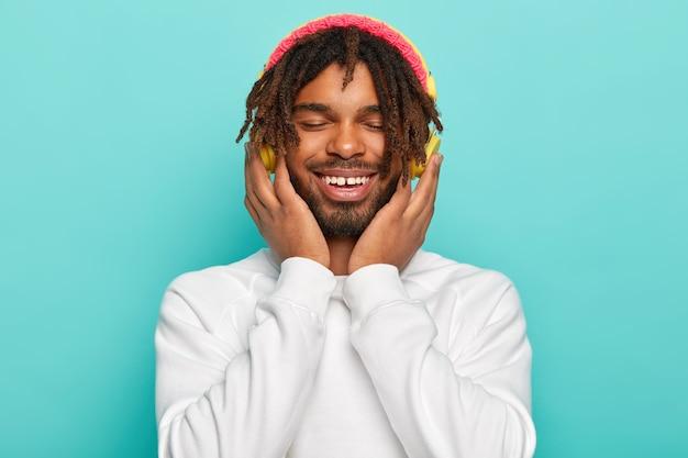 Nahaufnahmeporträt des begeisterten sorglosen männlichen modells hält hände auf kopfhörern, genießt cooles lied, lächelt breit, hat angst, gekleidet in weißen pullover und rosa hut, froh und entspannt