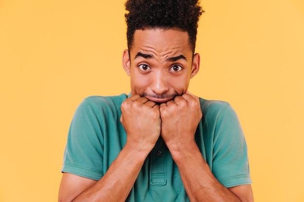 Nahaufnahmeporträt des besorgten kerls mit stilvollem haarschnitt. foto des verängstigten schwarzen mannes lokalisiert.