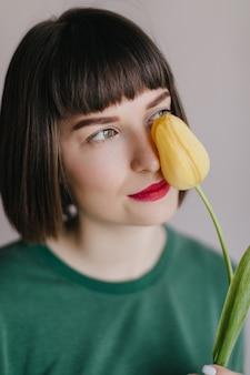 Nahaufnahmeporträt des bezaubernden brünetten weiblichen modells in der grünen kleidung schnüffelt tulpe. sorglose frau mit kurzem haarschnitt, der mit blume aufwirft.