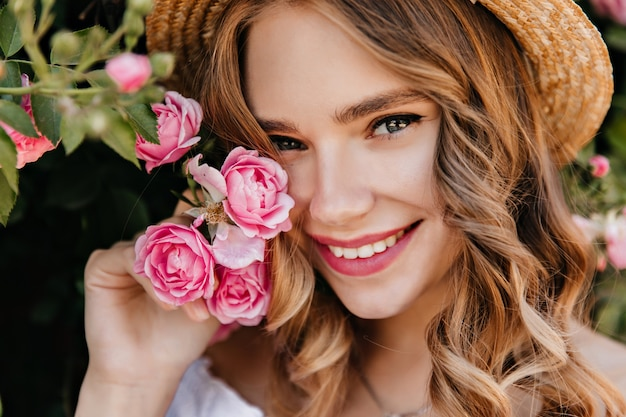 Nahaufnahmeporträt des bezaubernden mädchens mit den glänzenden augen, die mit blume aufwerfen. spektakuläre blonde frau im hut, die rosa rose hält und lächelt.