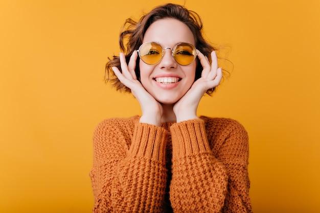 Nahaufnahmeporträt des blassen kaukasischen mädchens mit dem schönen lächeln. foto der entspannten europäischen frau trägt runde gelbe sonnenbrille.
