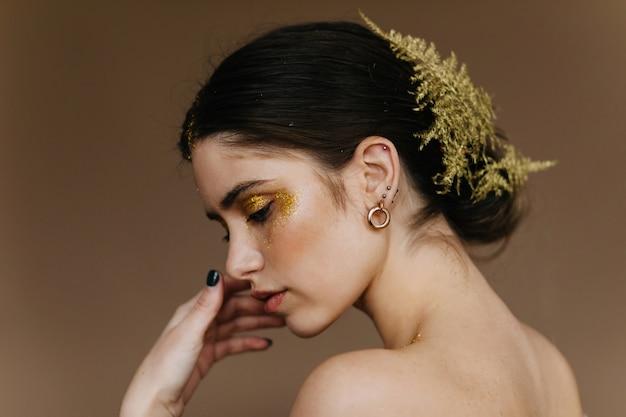Nahaufnahmeporträt des blithesome mädchens mit blume im haar. sorglose schwarzhaarige weiße frau.