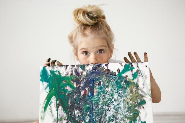 Nahaufnahmeporträt des blonden europäischen kleinen mädchens mit haarknoten und großen blauen augen, die ihr bild demonstrieren.