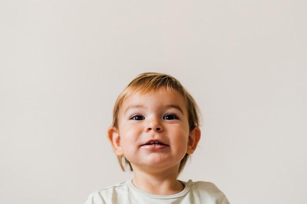 Nahaufnahmeporträt des blonden europäischen lächelns des kleinen mädchens