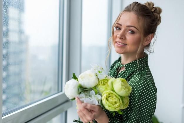 Nahaufnahmeporträt des blonden glücklichen mädchens, das einen blumenstrauß von pfingstrosen hält und die kamera betrachtet.