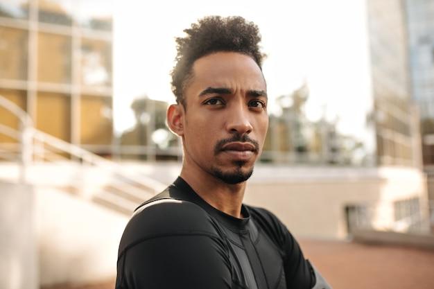 Nahaufnahmeporträt des braunen jungen dunkelhäutigen mannes im schwarzen sport-t-shirt sieht gerade aus