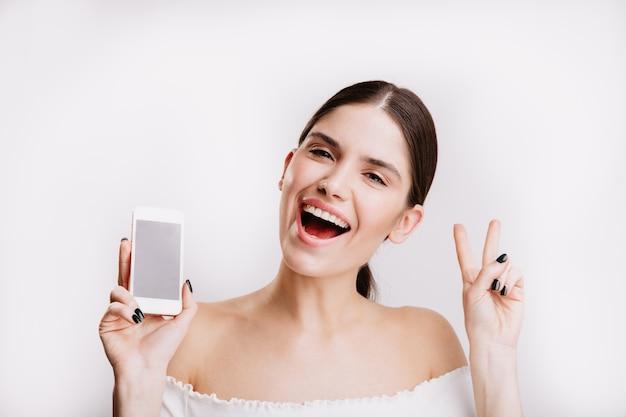 Nahaufnahmeporträt des brünetten mädchens mit telefon in ihren händen. junge frau zeigt friedenszeichen auf weißer wand.