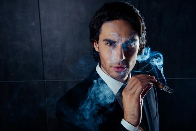 Nahaufnahmeporträt des brutalen gutaussehenden mannes, der eine zigarre mit rauch hält