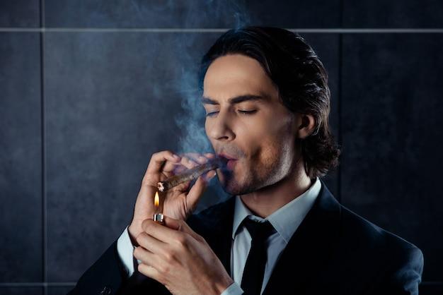 Nahaufnahmeporträt des brutalen jungen mannes zündet eine zigarre an