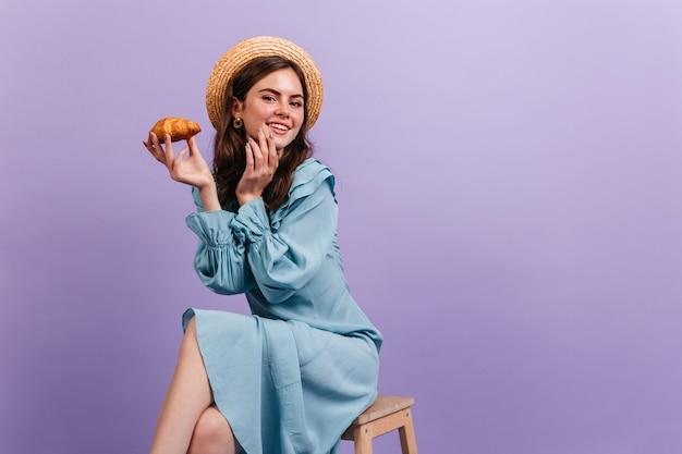 Nahaufnahmeporträt des charmanten mädchens, das mit croissant aufwirft. modell im bootsfahrer und im blauen seidenkleid niedlich lächelnd.