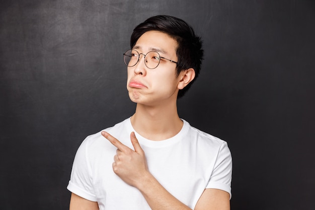 Nahaufnahmeporträt des eifersüchtigen und düsteren asiatischen jungen mannes, der bedauern empfindet, etwas aufregendes betrachtet, schmollend zeigt finger nach links zeigt, lust etwas hat, es sich aber nicht leisten kann,
